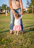 Baby girl learning to walk over a grass park Stock Images