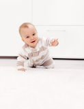 Baby girl learns to crawl Stock Photos