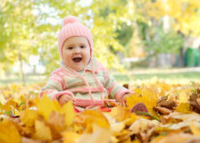 Baby girl in the leaves. Screaming little girl sitting in the autumn leaves in the park royalty free stock images