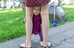 The baby girl is between legs of the mother royalty free stock image