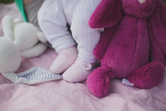Baby girl legs with stuffed toy on blanket Royalty Free Stock Photo
