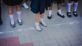Baby girl legs in white golf and beautiful shoes are in the lineup on the school line on September 1. September 1 - line royalty free stock image
