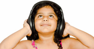 Baby girl listening music. A baby girl listening music on headphone Royalty Free Stock Photo