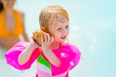 Baby girl listening sound of sea in shell Royalty Free Stock Photo