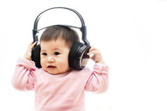 A baby girl listens music with headphone with hands Royalty Free Stock Image