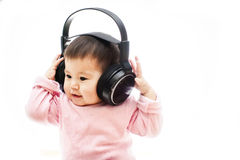 A baby girl listens music with headphone with hands Royalty Free Stock Photo