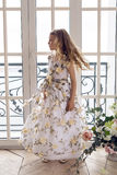 Baby girl in a long floral dress stands royalty free stock photos