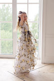 Baby girl in a long floral dress stands stock photos