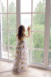 Baby girl in a long floral dress stands royalty free stock image