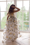 Baby girl in a long floral dress stands royalty free stock photo