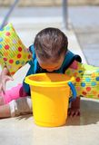 Baby Girl looking into bucket Stock Photos