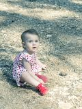 Baby girl looking at camera with expressive blue eyes. She is si. Tting on the ground royalty free stock photography