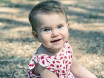 Baby girl looking at camera with expressive blue eyes. She is si. Tting on the ground stock photo