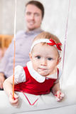 Baby girl looking at camera with father on background Royalty Free Stock Photos