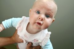 Baby Girl Looking at Camera. A 3 month old newborn baby girl is looking down at the camera as her father lifts her over his head while playing at home royalty free stock photo