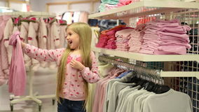 Baby girl looking at clothes in fashionable shop stock video