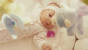 Baby girl looking at defocused toy mobile in her cot Royalty Free Stock Photo