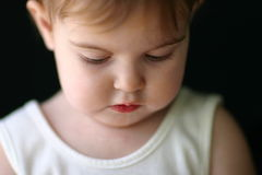 Baby Girl Looking Down. Young child looking down innocently stock photography