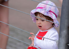 Baby girl looking through the fence Royalty Free Stock Photo