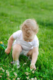 Baby girl looking for flowers in grass Stock Photo