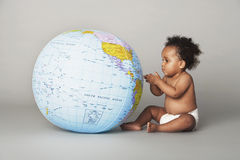 Baby Girl Looking At Inflatable Globe Stock Images
