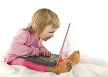 Baby girl looking onto the laptop's screen. On white background Royalty Free Stock Images