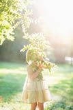 Baby girl looking out through tree foliage Royalty Free Stock Image
