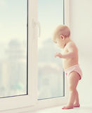 Baby girl looking out the window longing, sadness, and waiting. A baby girl looking out the window longing, sadness, and waiting Royalty Free Stock Photos