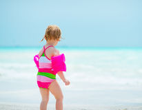 Baby girl looking on sea. rear view. Baby girl in swimsuit looking on sea. rear view Stock Images