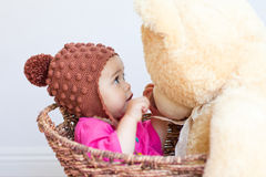 Baby girl looks at face of teddy bear Stock Images