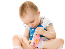 Baby girl looks at his shoe. royalty free stock photos