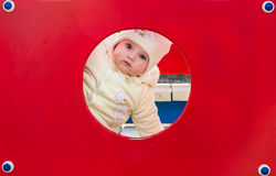 Baby girl looks in round red hole on the playground. Baby girl looks in round red hole Royalty Free Stock Photography