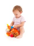 Baby girl lost in playing. Cute baby girl lost in playing with soft toy stock photography