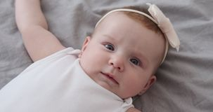 Baby girl lying on bed. Cute baby girl lying on bed at home stock video