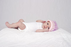 Baby girl lying on bed. Portrait of an alert looking  four week old baby girl lying on a bed covered with a white blanket wearing a pink knitted hat Royalty Free Stock Photo