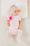 Baby girl lying in bed Stock Photos