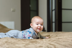 Baby girl lying on belly and grimacing Stock Image