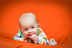 Baby girl lying on a belly on an orange pillow. Baby girl in a white pjama with big dots lying on a belly on an vibrant orange pillow Royalty Free Stock Images