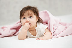 Baby girl lying on blanket at home Stock Images