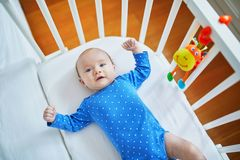 Baby girl lying in co-sleeper attached to parents` bed Stock Image