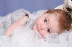 Baby girl lying on a fabric. Six-month beautiful charming girl on the couch royalty free stock photography