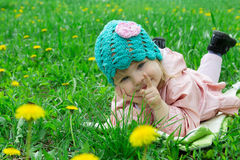 Baby girl lying among field of dandelions Stock Photos