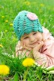 Baby girl lying among field of dandelions Stock Images