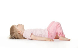 The baby girl is lying on the floor Stock Image
