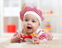 Baby girl lying on the floor and plays with toy indoor Stock Photography