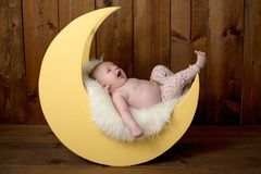 Baby Girl Lying on a Moon Shaped Photo Prop Stock Image