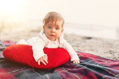 Baby girl lying on red blanket outdoor. Selective focus on her eyes. royalty free stock photos