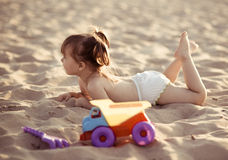 Baby girl lying in the sand on the beach Stock Photo