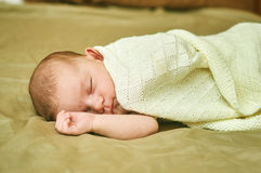 Baby girl lying on the sofa and covered with a shawl Royalty Free Stock Photo