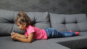 Baby girl lying on sofa with tablet. Little girl lying playing on tablet stock video footage